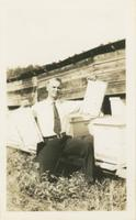John W. Oliver posing with beehives