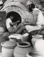 Mary Engle and Barry Crowder prepare pottery for firing.