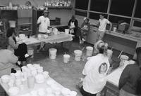 Instructor and students in pottery class.