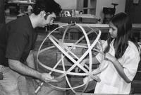Arrowcraft instructor and student construct a spherical wooden frame.