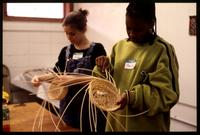 Girls working on basket weaving.