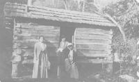 Mary Pollard and two women by a mountain cabin.