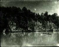 Two canoes on a large river by bluffs
