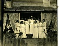 Group of female students posed on a front porch