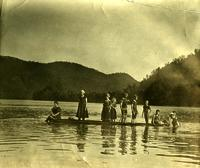 Children dressed in bathing suits on a platform in a river