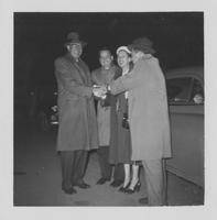 Estes Kefauver, two men and a woman join hands in cheer in front of car