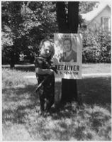 Hammer-holding toddler stands with Estes Kefauver campaign poster tacked to tree