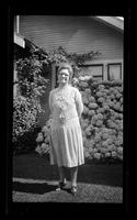 Untitled, woman in front of bushes