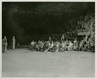 Large group of adults sitting on benches in cave