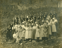 Large group in front of cave