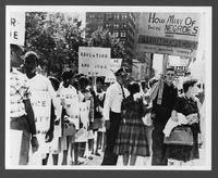 Black civil rights activists march while segregationists protest
