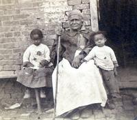 Betty Jackson in front of a slave cabin with two little girls