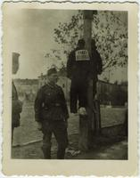 Two men hanging from pole with Russian placard