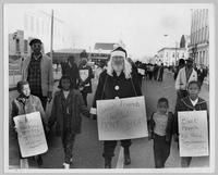 "White ""Santa Claus"" walks with four black children during Economic Boycott march"