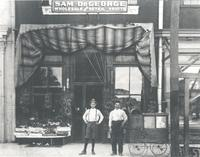 Salesman Walter Brown on the left and Sam DeGeorge on the right in front of a fruit store