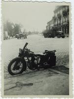 Motorcycle parked at curb, military vehicles in background