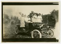 [Photograph of a home demonstration agent sitting behind the wheel with six girls in an automobile.]