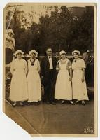 [Photograph of one man standing outdoors posting for photograph with four young women in their canning club uniforms]