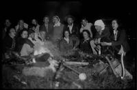 Campfire just outside Cabin in Greenbrier. Top Row: Chas. Gibson - West Barber - Roger Howell - Herb Webster - Jim Webster; 2nd Row: Jesse Dempster - Dickerman - Mrs. Jim Webster - Harriett Foulkes. Others not identified