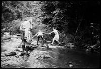 Mildred gets a hand in crossing stream in Tellico Area as Sonny Morris reaches for his camera, just in case